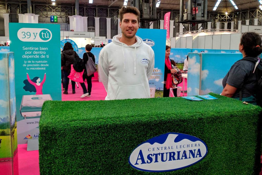 Uno de nuestros azafatos posa con el stand de Central Lechera Asturiana en la Carrera de la Mujer